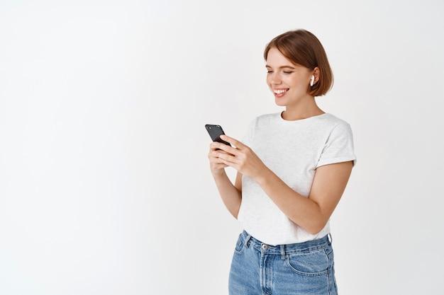 Молодая женщина слушает музыку в беспроводных наушниках, глядя на сообщение на мобильном телефоне, читает экран и улыбается, стоя у белой стены