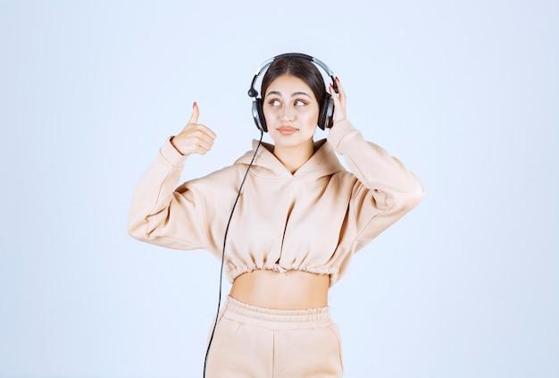 Giovane donna che ascolta le cuffie e che mostra il pollice in su