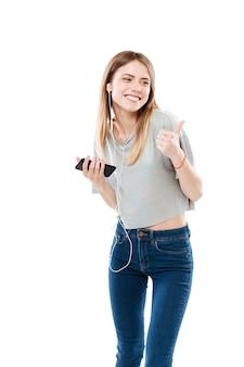 Молодая женщина прослушивания музыки и показывая большой палец вверх