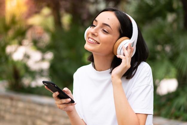 屋外で音楽を聴く若い女性