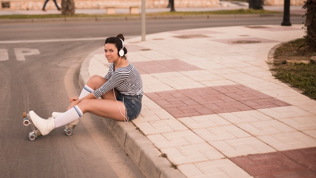 Young woman listening music on headphone relaxing on road