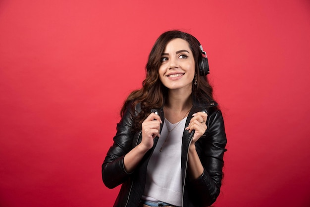 ヘッドフォンで音楽を聴き、赤い背景でポーズをとる若い女性。高品質の写真