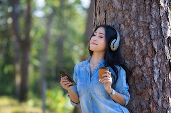 Young woman listening music in modern headphones communicating online  with cup of coffee