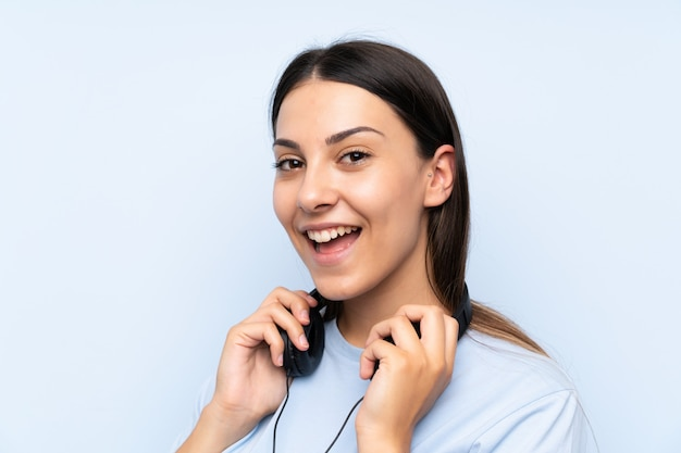 Young woman listening music over isolated blue wall