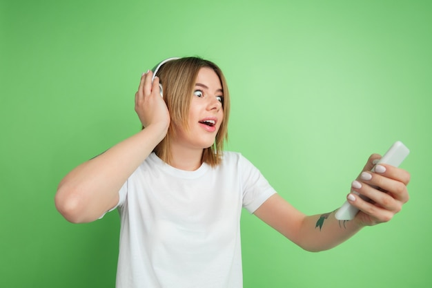 Young woman listening to music isolated on green studio wall