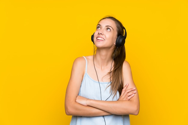 Young woman listening music over isolated yellow wall looking up while smiling
