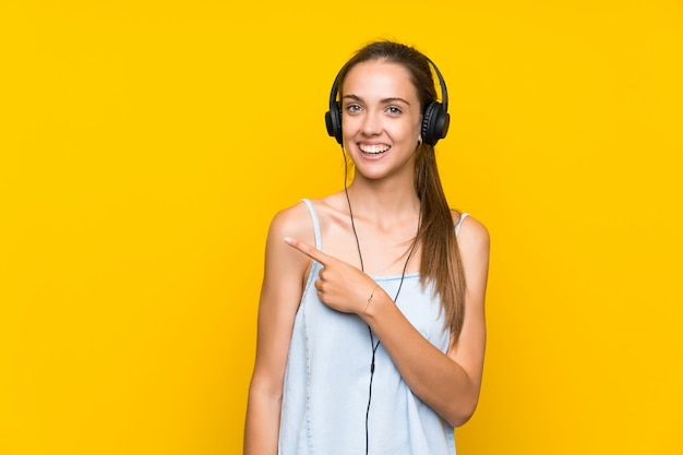 Young woman listening music over isolated yellow wall pointing to the side to present a product