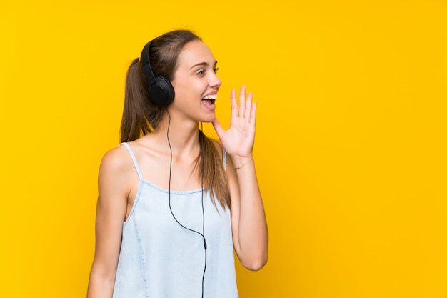 Young woman listening music over isolated yellow wall shouting with mouth wide open
