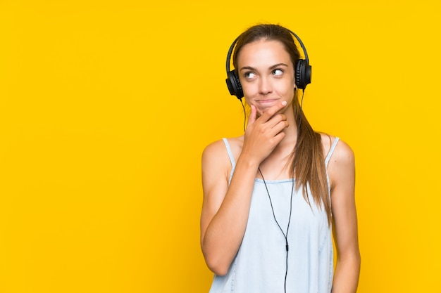 Young woman listening music over isolated yellow wall thinking an idea