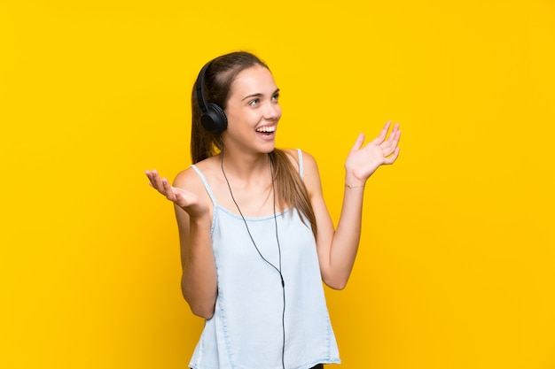 Young woman listening music over isolated yellow wall with surprise facial expression