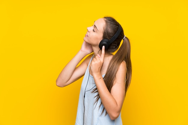 Young woman listening music over isolated yellow wall