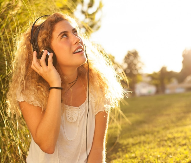 Young woman listening to music and looking up