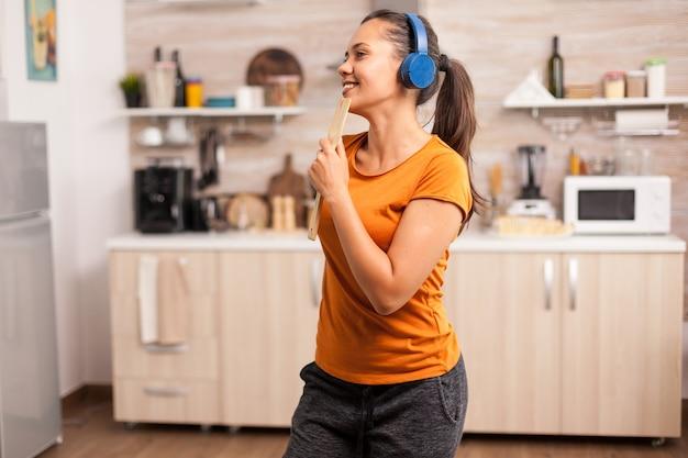 キッチンで木のスプーンで歌うヘッドフォンで音楽を聞いている若い女性