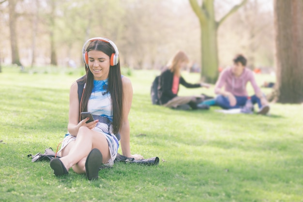 Young woman listening music at park in london