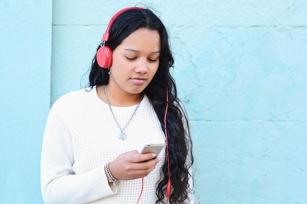 Young woman listening music and using her smartphone.