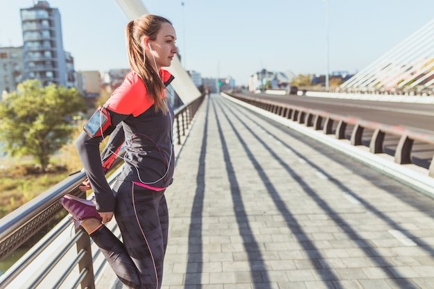 Young woman listening to music while stretching Free Photo