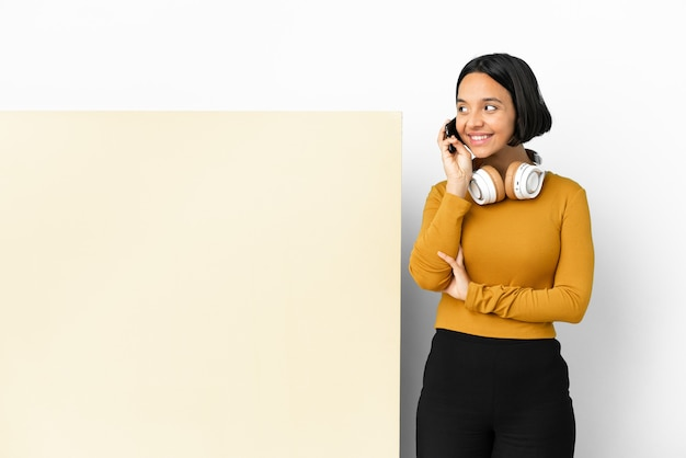 Молодая женщина слушает музыку с большим пустым плакатом, изолированным фоном, разговаривая с кем-то по мобильному телефону