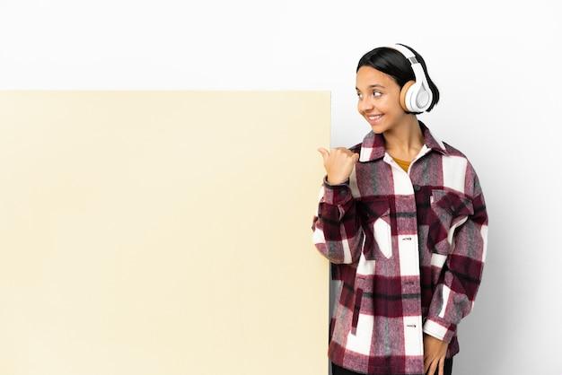 大きな空のプラカードで音楽を聴く若い女性が、製品を提示するために横を指している背景を分離