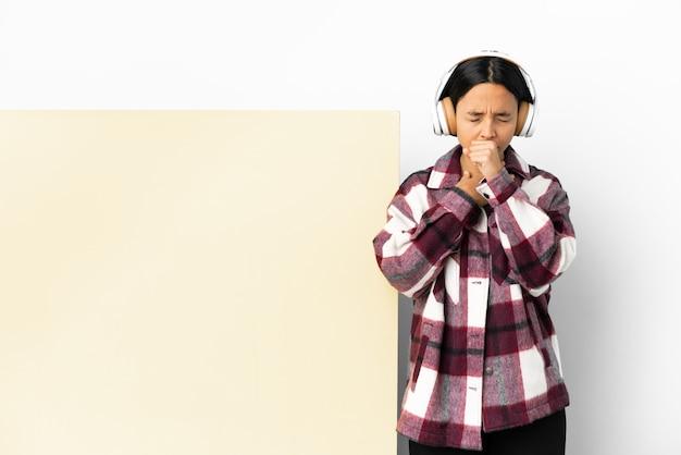 Молодая женщина слушает музыку с большим пустым плакатом на изолированном фоне и много кашляет
