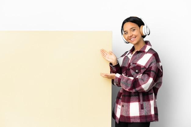 Молодая женщина слушает музыку с большим пустым плакатом на изолированном фоне, протягивая руки в сторону, приглашая прийти