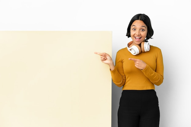 Молодая женщина, слушающая музыку с большим пустым плакатом на изолированном фоне, испугалась и указала в сторону
