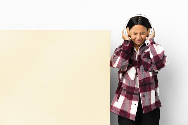 Молодая женщина, слушающая музыку с большим пустым плакатом на изолированном фоне, разочарована и закрывает уши