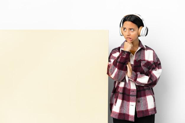 孤立した背景の上に大きな空のプラカードで音楽を聴いている若い女性は疑問を持って考えています