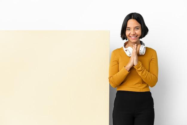 Молодая женщина, слушающая музыку с большим пустым плакатом на изолированном фоне, держит ладонь вместе. человек о чем-то просит