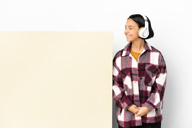 Молодая женщина слушает музыку с большим пустым плакатом на изолированном фоне, смотрящую сторону