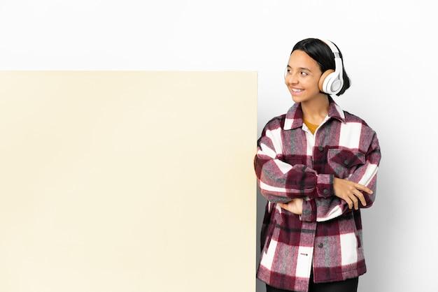 Молодая женщина, слушающая музыку с большим пустым плакатом на изолированном фоне, смотрит в сторону и улыбается