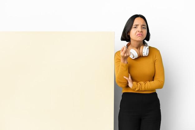 Молодая женщина слушает музыку с большим пустым плакатом на изолированном фоне, делая итальянский жест