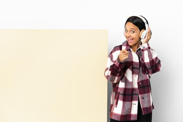Молодая женщина слушает музыку с большим пустым плакатом на изолированном фоне, делая жест телефона и указывая вперед