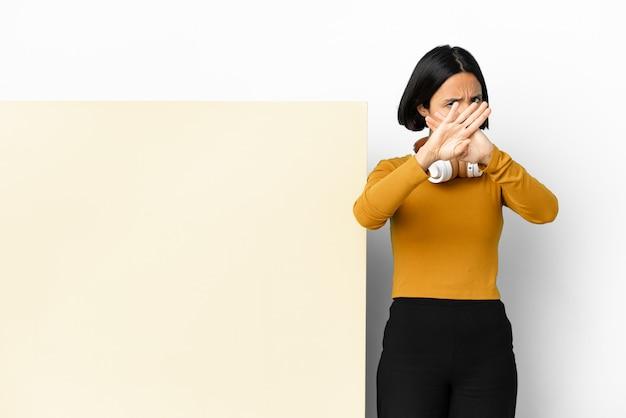 Молодая женщина слушает музыку с большим пустым плакатом на изолированном фоне, делая жест рукой, чтобы остановить действие