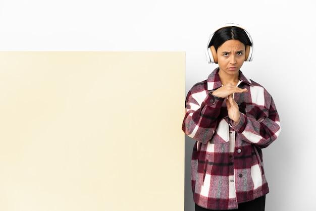 Молодая женщина слушает музыку с большим пустым плакатом на изолированном фоне, делая жест тайм-аута
