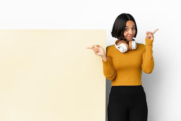 Молодая женщина слушает музыку с большим пустым плакатом на изолированном фоне, указывая пальцем на боковые стороны и счастливая