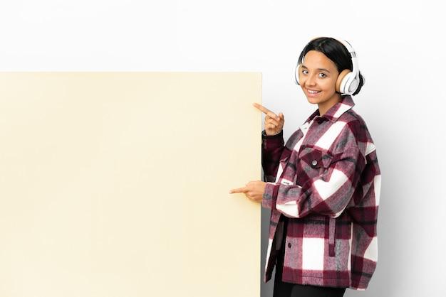 横に指を指し、製品を提示する孤立した背景の上に大きな空のプラカードで音楽を聞いている若い女性
