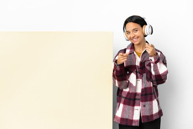 Молодая женщина слушает музыку с большим пустым плакатом на изолированном фоне, указывая на фронт со счастливым выражением лица