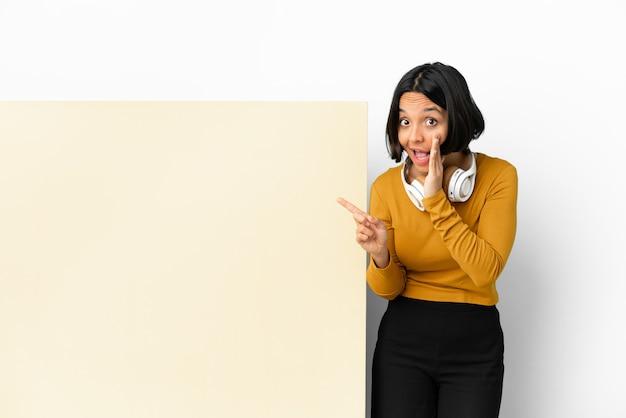 Молодая женщина слушает музыку с большим пустым плакатом на изолированном фоне, указывая в сторону, чтобы представить продукт, и что-то шепчет