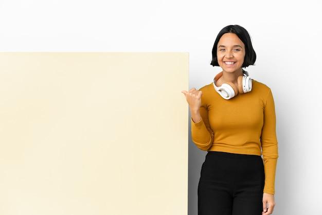 製品を提示する側を指している孤立した背景の上に大きな空のプラカードで音楽を聞いている若い女性