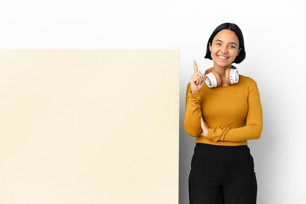 Молодая женщина слушает музыку с большим пустым плакатом на изолированном фоне, указывая на отличную идею