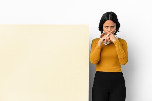 Молодая женщина слушает музыку с большим пустым плакатом на изолированном фоне, показывая знак жеста молчания