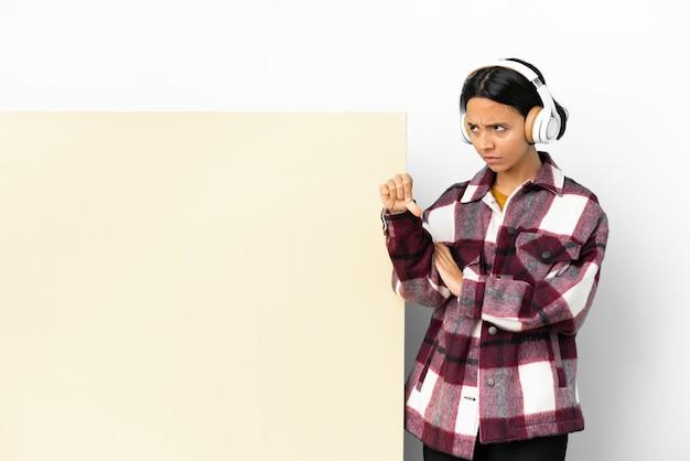 Молодая женщина слушает музыку с большим пустым плакатом на изолированном фоне, показывая большой палец вниз с отрицательным выражением лица