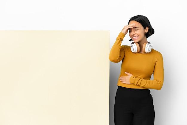 Молодая женщина слушает музыку с большим пустым плакатом на изолированном фоне, много улыбаясь
