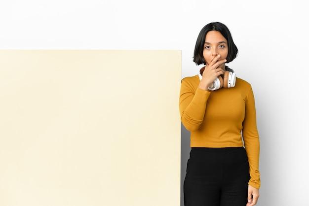 Молодая женщина, слушающая музыку с большим пустым плакатом на изолированном фоне, удивлена и шокирована, глядя вправо