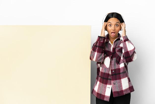 Молодая женщина слушает музыку с большим пустым плакатом на изолированном фоне с выражением удивления