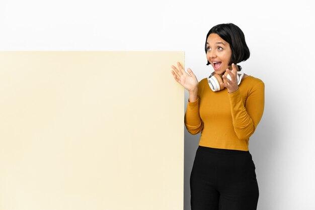 Молодая женщина слушает музыку с большим пустым плакатом на изолированном фоне с удивленным выражением лица