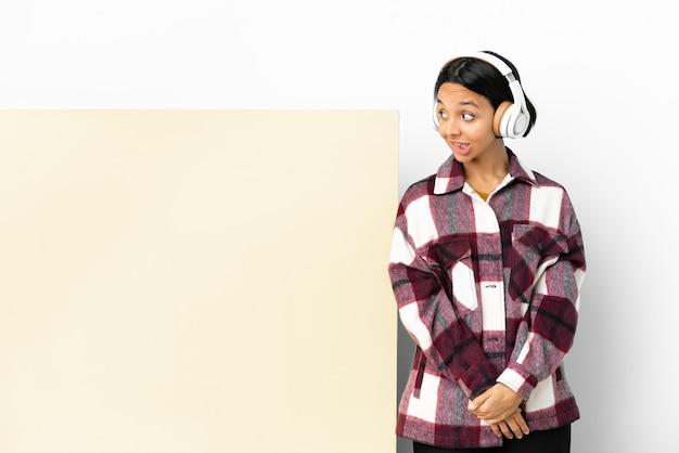 見上げている間疑いを持っている孤立した壁の上の大きな空のプラカードで音楽を聞いている若い女性
