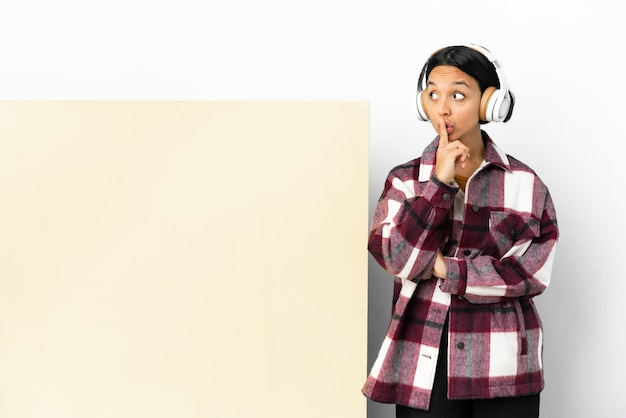 입에 손가락을 넣어 침묵 제스처의 표시를 보여주는 고립 된 벽 위에 큰 빈 현수막으로 젊은 여자 듣기 음악