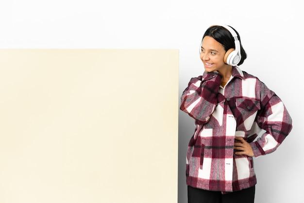 アイデアを考えて孤立した壁の上の大きな空のプラカードで音楽を聞いている若い女性