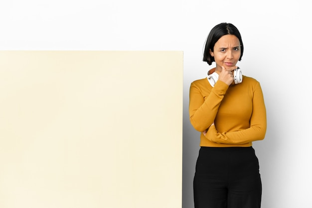 Young woman listening music with a big empty placard isolated background thinking